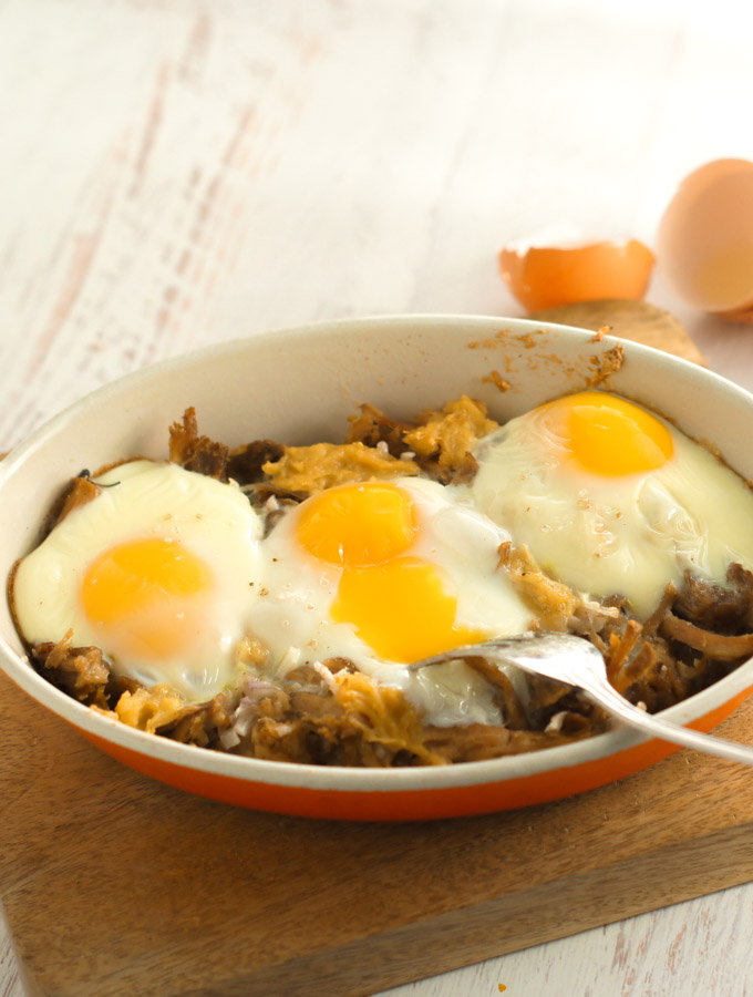 three runny eggs baked in a shallow orange dish with leftover pulled pork