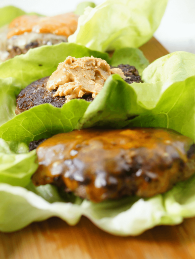 Three burgers cooked on the stove, plated in a row with lettuce topped with cheese and peanut butter.