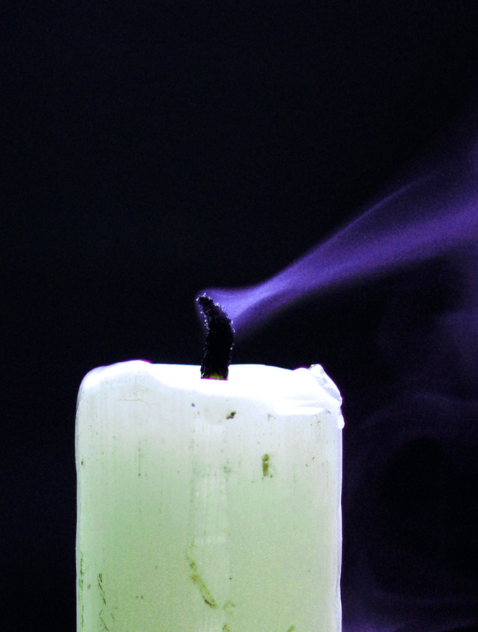 A white candle blown out in a dark room.