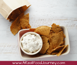 Caramelized onion dip in a small bowl with chips on the side