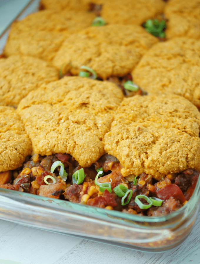 Gluten free cornbread cooked over the top of chili in a glass casserole dish.