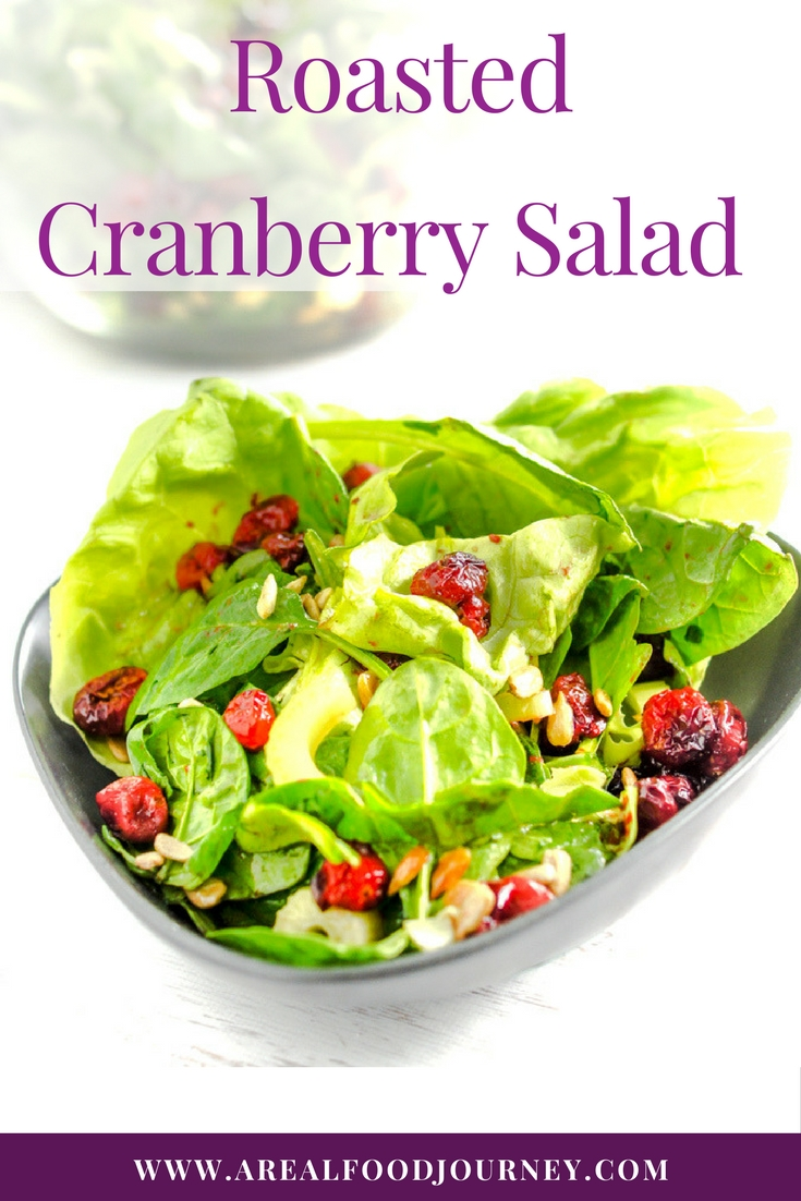 A fresh spring salad with butter lettuce and roasted cranberries on top with seeds and a light healthy dressing