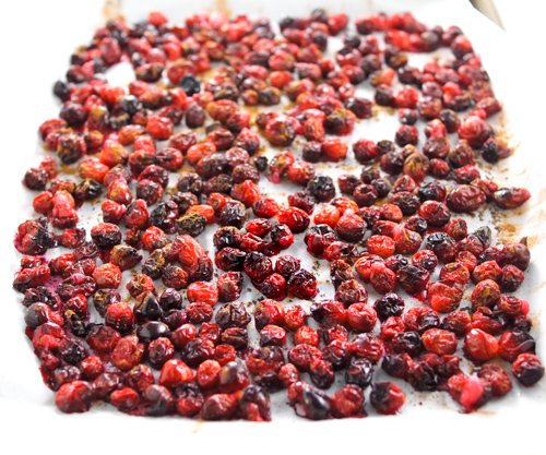 Roasted cranberries bright red on parchment after roasting