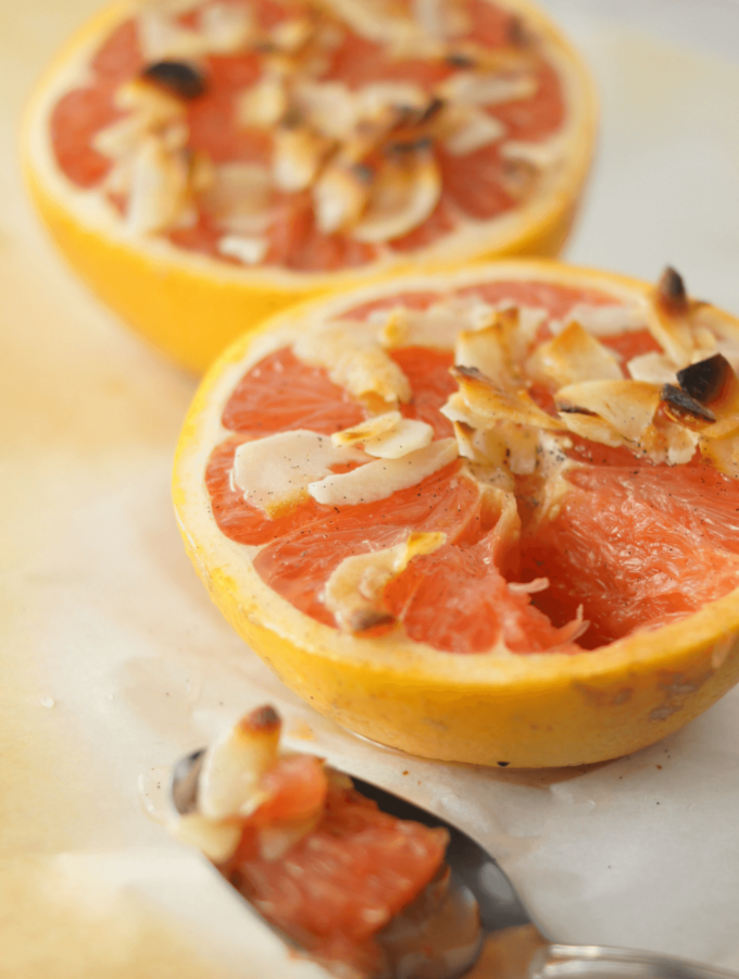 Two cute halves of ruby grapefruit baked with honey, vanilla bean and coconut flakes on parchment.