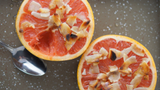 honey baked grapefruit with coconut flakes on a steel try with a silver spoon.