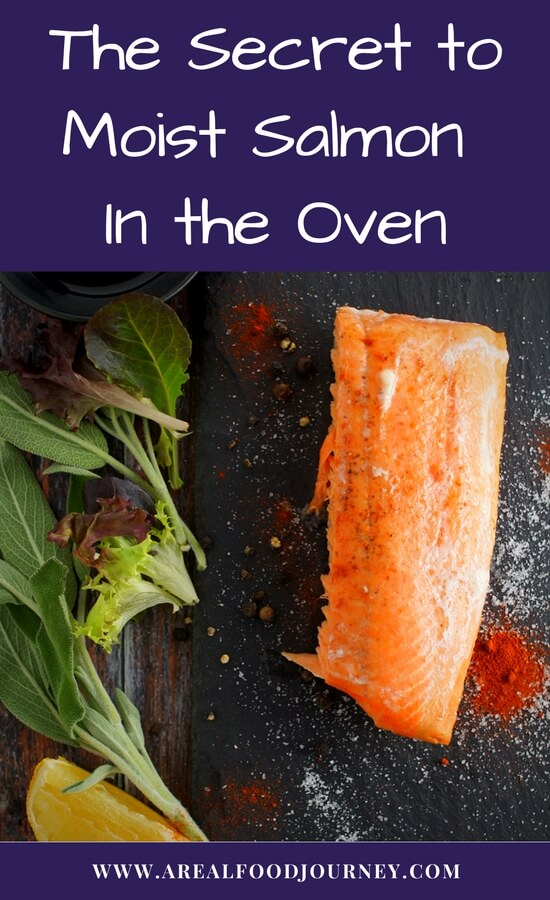 Oven baked salmon on a slate background sprinkled with smoked salt and paprika with a side of mix greens.
