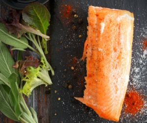 A strip of salmon surrounded in spices with baby greens and herbs on a slate tile