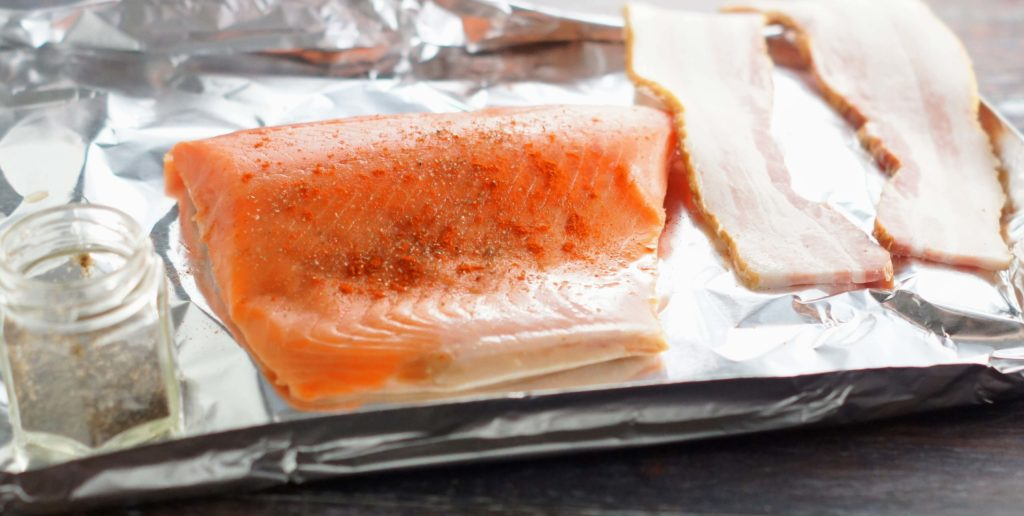 Raw Salmon sprinkled with paprika and smoked salt on a foil try with bacon ready for the oven.
