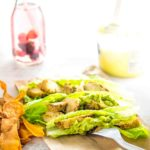 flame grilled chicken chopped on small romain lettuce boats topped with guacamole, with a side of sweet potato chips a drink with berries and lemon curd yogurt.