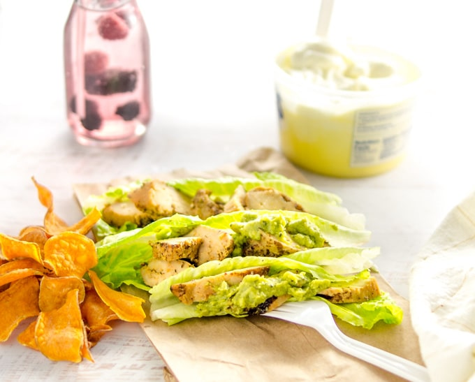 A road trip lunch of chicken on lettuce boats on a paper bag with orange sweet potato chips.