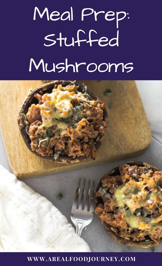Sausage stuffed mushrooms on a wodden cutting board topped with cheese.