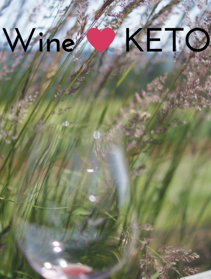 a wine glass over a green field- can you have wine on the keto diet?