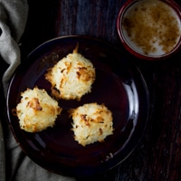 Three low carb coconut macaroons on a dark plate with milk