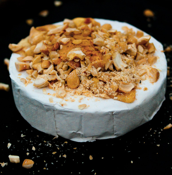 wheel of brie cheese with cashews on top.