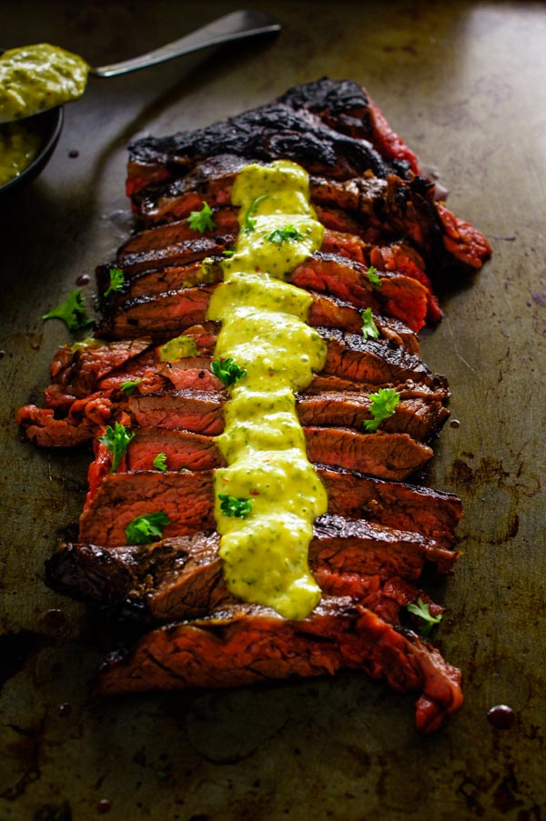 Sliced flank steak with chimichurri aioli over the top on a sheet pan