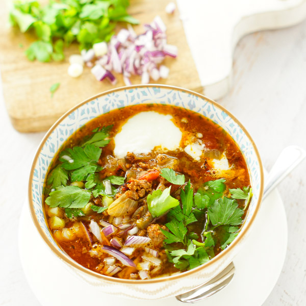 keto paleo taco soup in a small bowl with sour cream and cilantro on top